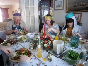 Eating Christmas dinner, wearing cracker hats