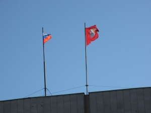 Russian and Sevastopol flags flying over a local government building