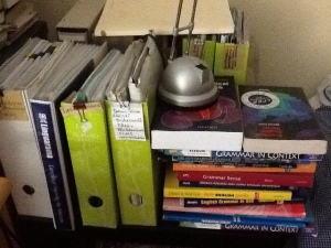 Temporary bookshelf (binders and a pile of grammar books)