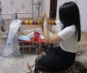 Demonstrating how a baby can be strapped into a traditional Kazakh crib