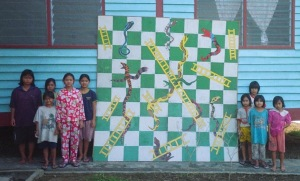 Borneo kids with Snakes and Ladders board