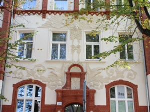 Building in Bydgoszcz decorated with a face and sunbeams in relief