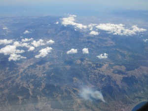 A volcano smoking in the bottom right-hand corner. The rest of the view is mountains with a few cotton-wool clouds over them