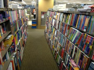 A corridor between two long bookshelves filled with coursebooks