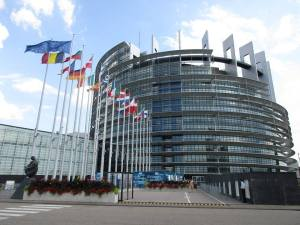 EU Parliament, with flags of all of the current EU nations flying in front of it