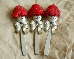 Three teaspoons lying side by side, each with a raspberry hat, a face painted on, and a little silver bow