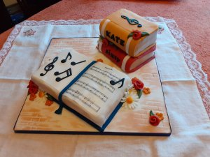 A birthday cake made of an open book with music notes at the front, and a 'pile' of two books at the back with 'Kate' and 'sixty' written on the spine