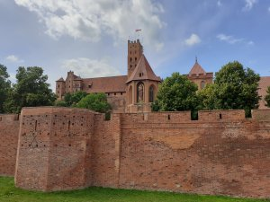 Malbork Castle - a red-brick fortress with a wall in the foreground, a church in the middle and a tall central tower in the background